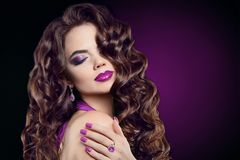 Brunette with long curly hair, violet makeup, manicure nails, am. Ethyst jewelry. Attractive cute model with lips, healthy frizzy shine hairstyle isolated purple stock photos