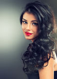 Brunette with long,dense curly hair. Portrait.Model brunette with long,dense curly hair and bright lipstick.  Tender smile Royalty Free Stock Photos