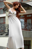 Brunette in long dress near old-fashioned hotel Stock Image