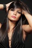 Brunette with long hair posing on black. Stock Photo