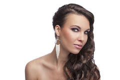 Brunette with long hair,silver earring. Fashion shot of a cute young brunette with long hair and naked shoulder isolated on white background Royalty Free Stock Images