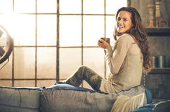 A brunette long-haired woman in a loft living room. A brunette long-haired woman is seen from the side while sitting on the back of a sofa. She  is smiling and Stock Images