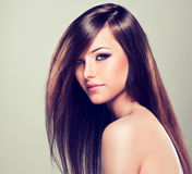 Brunette with long straight hair. Brunette girl with long straight hair. Fashionable hairstyle and makeup. Sincere look Royalty Free Stock Photo
