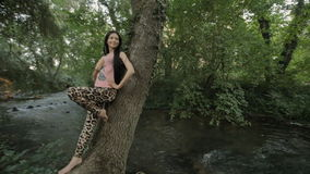 Brunette with long straight hair rests on a tree stock video