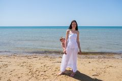 Brunette in long transparent dress with her son on the beach. In full growth Stock Photos