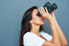 Brunette looking through binoculars Royalty Free Stock Images