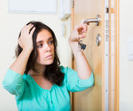 Brunette looking at broken lock of door Stock Photography