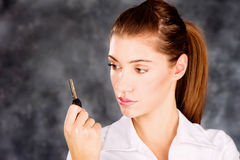 Brunette looking at a key. Pretty brown eye brunette looking at a key in her right hand, wearing white blouse. Focus on key Royalty Free Stock Photos