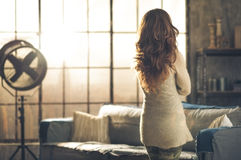Brunette looking out industrial chic loft window. Seen from behind, a brunette woman in comfortable clothing is standing in a loft living room, looking out the Stock Images