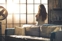 Brunette looking out of urban loft window. Looking away, a brunette woman in comfortable clothing is standing in a loft living room, hugging herself, looking out Stock Photo