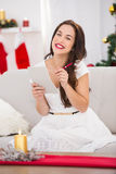 Brunette lying on the couch writing her christmas list Royalty Free Stock Photography