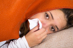 Brunette lying down under orange blanket and blowing her nose, sick with flu concept Stock Photo