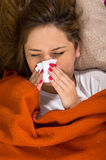 Brunette lying down under orange blanket and blowing her nose, sick with flu concept Royalty Free Stock Photography