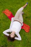 Brunette lying in the grass Royalty Free Stock Photos