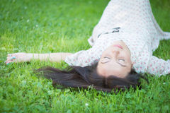 Brunette lying in the grass. Stock Photos