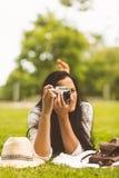 Brunette lying on grass taking photo Stock Photos