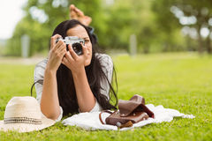Brunette lying on grass taking picture Stock Images