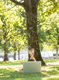 Brunette lying on the grass using her laptop Royalty Free Stock Photos