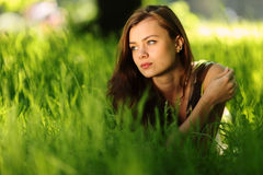 Brunette lying on green grass Royalty Free Stock Photo
