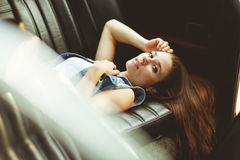 Brunette lying on leather seat of car. tinted photo. Brunette with long hair lying on leather seat of car. tinted photo Royalty Free Stock Photography