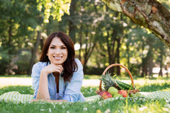 Brunette lying on a mat with basket full of fruits in the park Stock Photo