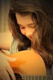 Brunette Mädchen, das Gitarre spielt Lizenzfreies Stockfoto