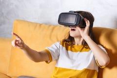 Brunette Mädchen, das VR-Gerät prüft stockbild