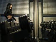 Brunette Mädchen der Eignung in der schwarzen Sportkleidung, die das Regal mit Dummköpfen in der Turnhalle an gegen den Spiegel b stockbild