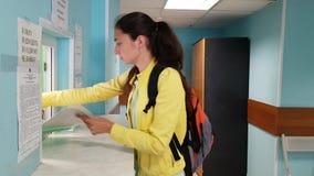 Brunette Mädchen in einer Jacke und in einem Rucksack steht vor einem Windows und verständigt sich mit dem Angestellten stock footage