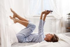 Brunette Mädchen im hellblauen Pyjama legt mit ihren Beinen oben auf das Himmelbett auf das graue Blatt mit beige Decke und lizenzfreie stockbilder