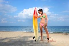 Brunette-Mädchen mit einem Surfbrett Stockfoto