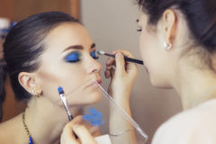 Brunette make up artist woman applying make up for a brunette mo Royalty Free Stock Photography