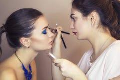 Brunette make up artist woman applying make up for a brunette mo Stock Photo