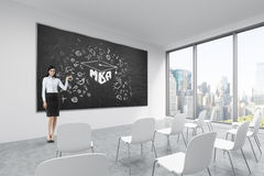 A brunette makes a presentation in a classroom in a modern university or fancy office. White chairs, a black chalkboard on the wal Stock Photo