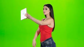 Brunette making photo using a tablet pc. Green screen studio. Brunette making photo using a tablet pc, girl dressed in a red t-shirt, woman holds in hand tablet stock footage