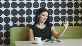 Brunette making selfie photo using a mobile phone. Brunette girl making selfie photo using a mobile phone during coffee break stock footage