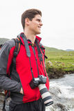 Brunette man on a hike with a camera around his neck Stock Images