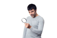 Brunette man looking with magnifying glass Royalty Free Stock Images