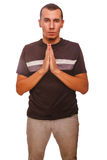 Brunette man prays Christianity hands together Stock Photo