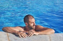 Brunette man relaxing inside the swimming pool Greece - greek summer photos stock photo