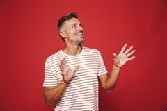 Brunette man in striped t-shirt rejoicing and looking aside at c royalty free stock photo