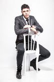 Brunette man in suit and tie sitting on white chair Royalty Free Stock Photography