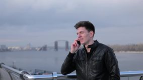 Brunette man talking on mobile phone on a background of the urban river.  stock footage