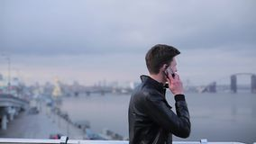 Brunette man talking on mobile phone on a background of the urban river.  stock video