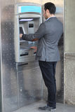 Brunette man withdrawing money Royalty Free Stock Image