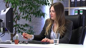 Brunette manager works in the office with documents. And drinks water stock video