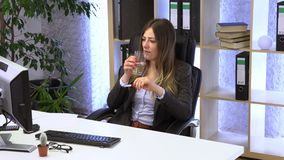 Brunette manager works in the office with documents. And drinks water stock footage