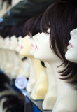 Brunette mannequins with wigs on shelves of hair salon Royalty Free Stock Photo