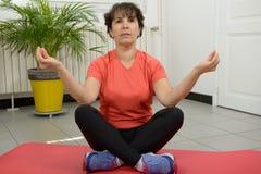 Brunette mature woman doing yoga exercises Royalty Free Stock Photos