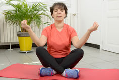 Brunette mature woman doing yoga exercises. A brunette mature woman doing yoga exercises Royalty Free Stock Photography